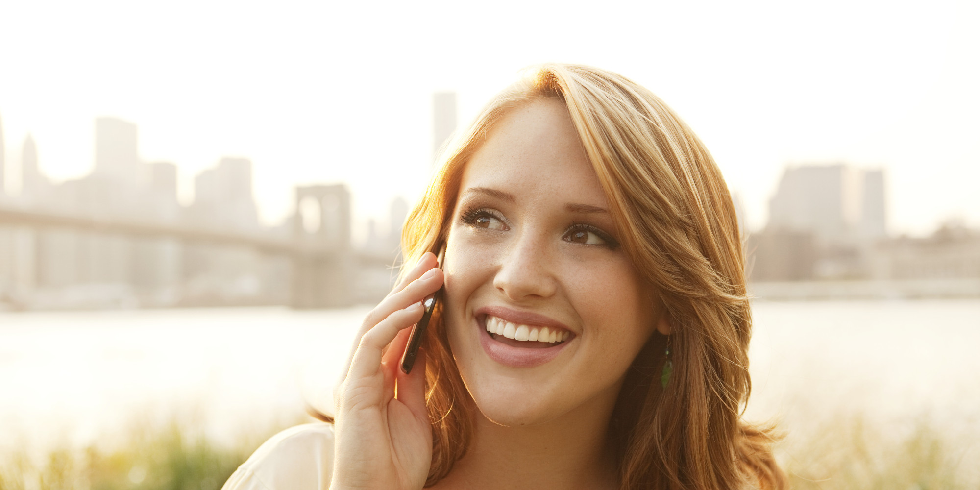 Young Woman, Smiling, using cell phone outdoors
